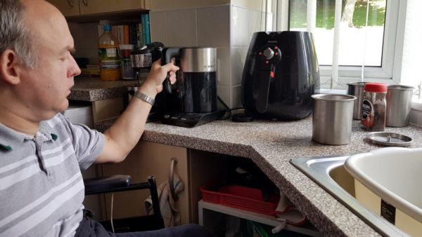 A man in a wheelchair reaches for a kettle on a lowered kitchen counter